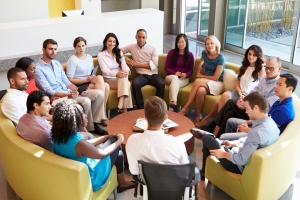 Multi-Cultural Office Staff Sitting Having Meeting Together